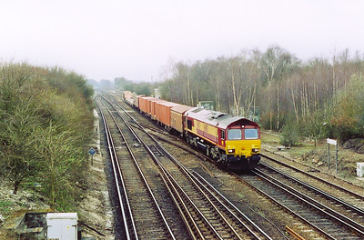 An EWS freight working approaches the foot bridge at Worting Junction with 66198 rostered to 6V38 1103 Marchwood to Didcot MOD stores.  A variety of wagons form the payload from the MOD site at Marchwood off the Fawley branch, see later on.