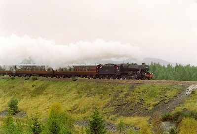 After passing over the 1,315 foot summit at Slochd, it is downhill to Aviemore. Here 48151 is seen passing the tall embankment just to the south of Carr Bridge falling at 1 in 100 with steam on. There is a short rise at 1 in 100 not far from here.