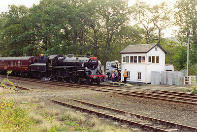 Pitlochry is reached about an hour late and another water stop is due. Co owner Peter Proud shovels coal forward in the tender as water is taken from a road tanker courtesy of the railtour sponsors, Whyte and MacKay Whisky. The former Highland Railway signalbox is stil in use.