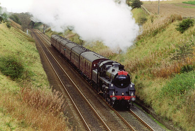 On 4/10/1997 BR Standard 4 75014 climbs the 1 in 102 1/2 gradient of Lochmuir Bank with a one way railtour from Edinburgh to Inverness.  The train is running late by this early stage.