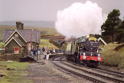 The usual water stop at Garsdale allows the chasing pack to get ahead again for another shot. After a short rise at 1 in 264 before the station and a level run through the platforms of Dent station, the line now falls at 1 in 264 for a short distance. The driver looks out from the right hand side of the loco.  4/4/1998