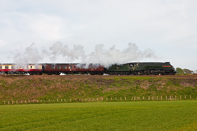 The loco passes by with a light steam exhaust despite the heavy load.