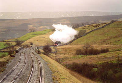 After the usual water stop at Garsdale, the train continues its climb to the summit at Ais Gill. Shortly after Garsdale is the short Moorcock Tunnel. 6024 bursts from the 98 yard long bore.