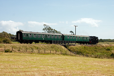 Moving slightly to a field at Woodyhyde between Afflington and Harmans Cross and former Swanage loco, now at the East Somerset Railway, USA Tank lookalike 30075 saunters past with two coaches on 2H08 1210 Norden to Harmans Cross.