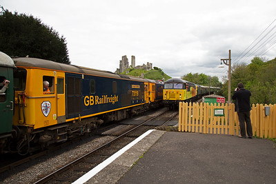 Four locos on two trains as the up and down workings pass each other under the ever guarding ruins of Corfe Castle.