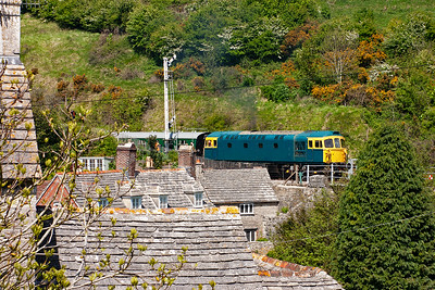 Type 3 push pull fitted class 33/1, 33111 powers up from a signal check at the down home and passes over Sandy Hills Lane with 2H12 1330 from Norden to Harmans Cross. The stone flagged roofs of the cottages form a beautiful foreground to the shot.