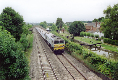 Another westbound empty stone working passes beside lock number 67. First generation General Motors 59004 in Yeoman livery fronts a rake of empty JHA bogie aggregate hoppers. The working is 7C31 0913 Theale to Merehead empties.