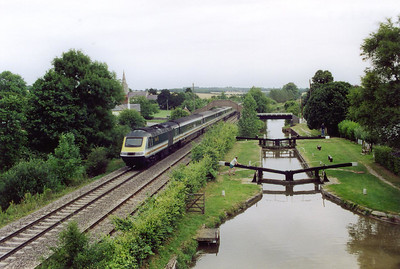 The chamber is almost full and the man waiting to the left will open the gate to allow his boat in. To the left an up HST passes by working 1A36 0622 Penzance to Paddington, passing below the footbridge over the railway and the cut.