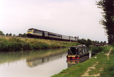 "The railway and the canal are close companions through the valley, they come together again at Crofton, several miles west of Little Bedwyn. 43035 fronts a down working to Plymouth, 1C23 1033 off London Paddington. The narrow boat ""Tobias"" is moored at the towpath."