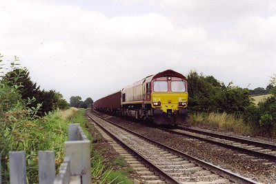 A level crossing close to Crofton is the location for 66189 working 7C48 1151 Appleford to Westbury Yard empty EWS bogie boxes.