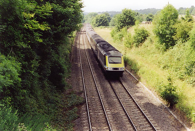 The summit of the Berks and Hants route is Savernake and an unidentified FGW HST passes the summit, the site of Savernake Low Level station and the junction of the line to Marlborough which closed on 18/4/1966. The canal passes below ground here in a shallow tunnel 502 yards long, as the landowner did not want a deep cutting on the canal on his land.  The western portal is to the right of the large tree to the right of the rear of the train.