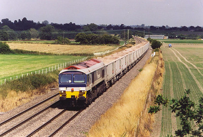 Moving further west again to a road over bridge near Manningford and the first train approaching is 59101 at the head end of 7V67 1033 Sevington to Merehead Quarry empty JNA boxes. At least two of the vehicles are still loaded.