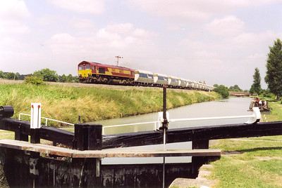 66032 is seen for the second time with a rake of empty JHA Hanson liveried bogie hoppers heading west with lock No 60 in the foreground. The train is unidentified.
