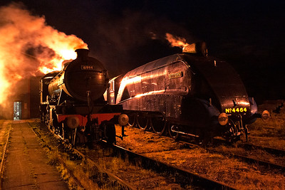The steam from 61994 is back lit by the shed light behind it and it also glints off the casing of 4464 by the firebox.