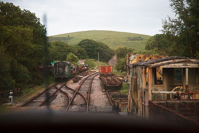 The area is now laid out with sidings for storing derelict stock.  In Southern Railway and BR service, this was the site of Eldon Sidings on the left where ball clay from the Norden Mines was transferred from narrow gauge wagons onto standard gauge ones for onward transport.