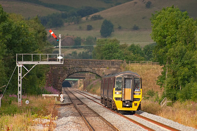 The black hole of the 2 mile 182 yard long Cowburn Tunnel, that burrows through the High Peak Hills, is visible in the distance as 158807 approaches working 1B66 0644 Manchester Piccadilly to Cleethorpes.