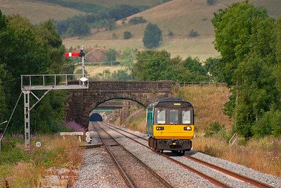 Pacer unit 142089 passes the down starter signal as it slows for its Edale stop with 2S06 0701 Manchester Piccadilly to Sheffield. In the background above the tunnel mouth can be seen the spoil brought to the surface from one of the few shafts sunk during the tunnel boring process. The shaft is now sealed.