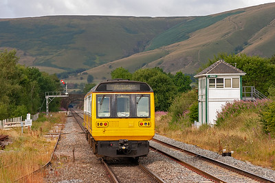 The pacer unit gets away and has the road with the controlling Edale signalbox to the right. The mass of the High Peak Hills lies ahead and this view gives an idea of the challenge the line builders had.