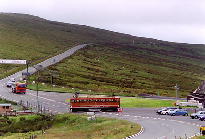 SMR No 4 crosses the road with a descending service from Snaefell Summit to Laxey.