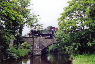 "The ducks on the right bank of the Silver Burn are undisturbed by the snorting ""peacock"" passing on the bridge above them. The train is the 1555 Douglas to Port Erin with No 10 in charge."