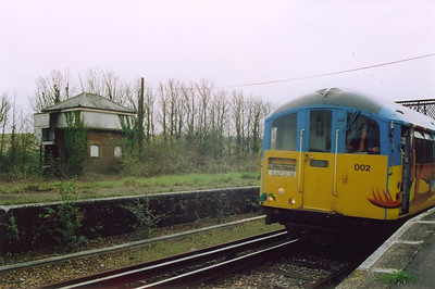 On the east side of the station is the boarded up shell of Brading signalbox. Unit 002 hums away from the station with the 1313 Shanklin departure.