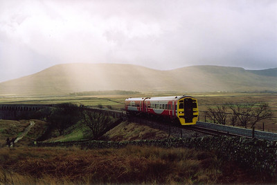 Shafts of sunlight stream down on Ingleborough and the land to the north as 158910 climbs north with 1M53 0949 Saturdays only class 1 working from Leeds to Carlisle. This train used to run to Glasgow Central but now terminates at the border city.