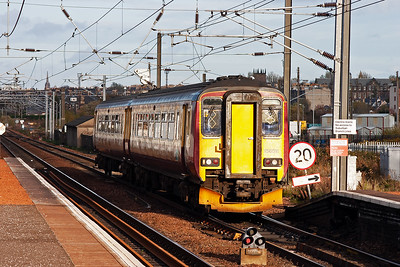 A class 2 local service slows for its station stop. 156511 forms 2Y45 1442 Edinburgh to Glasgow Central High Level.