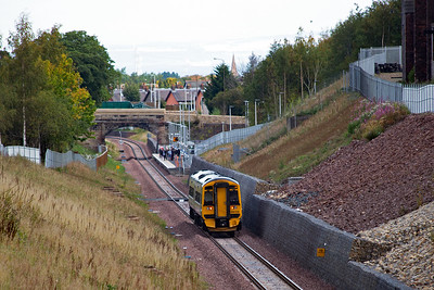 An Edinburgh bound train drops down grade and slows for its station stop at Newtongrange.  There are quite a few people on the platform, some may be waiting for this train but most will be waiting for the next one.  158728 forms 2T71 1028 Tweedbank to Edinburgh.