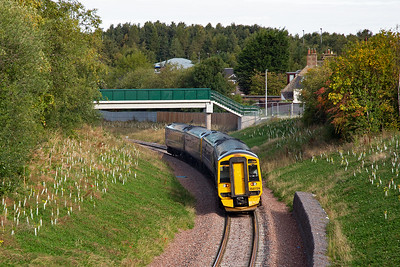 The original station has long been demolished and the area was landscaped after the tracks were relaid.  The units head for Edinburgh on a falling gradient here of 1 in 70.