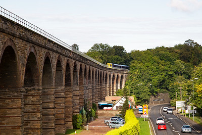 The viaduct was designed by John Miller and opened by the Edinburgh and Hawick Railway in 1849.  Today the double track wide deck carries just a single track.  A patch of sunlight catches the north end of Newbattle Viaduct as an unidentified class 158 sprinter comes out of the trees with 2T70 0922 off Edinburgh to Tweedbank.