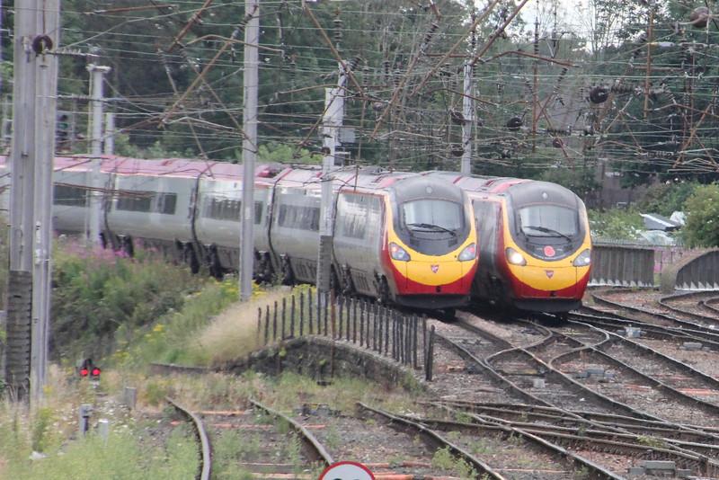 Pendolino 390 046 on 1M13 (1240 GLC to EUS) leaving Carlisle whilst passing Pendolino 390 103 on 1S52 (1030 EUS to GLC)  south of Carlisle. Carlisle 25 July 2015