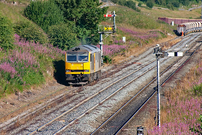 The shunter is waiting at the end of the rake for the loco to return and buffer up so he can couple the train.  The signals do not regulate this line but the main line to the right.