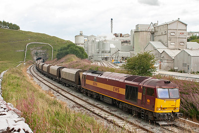 The brightness of the early morning has gone as 60094 lifts its loaded JEA hoppers past the vast white dust covered buildings of Tunstead Quarry. Even the stones of the wall in the bottom left are coated with white dust.