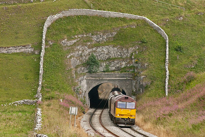 A dry stone wall rings the portal like a halo as 60094 slowly make its way up the hard 1 in 90 pull. The train working is 6F06 1525 Tunstead to Oakleigh loaded lime hoppers.