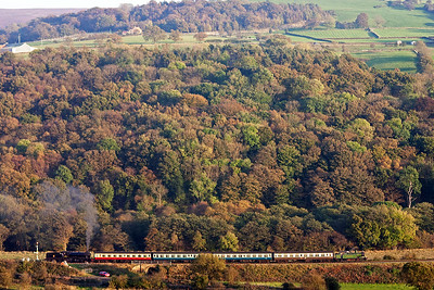 The autumnal colours on the leaves paint the trees a beautiful patchwork of greens and browns and all shades in between. There can not be a breath of air in the valley judging how high the smoke is rising above 61994's chimney as it drifts towards Grosmont.