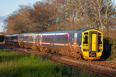 The first day of services in 2007 on the Far North Line and First Group liveried 158722 and 158704 slows for its Tain stop with 2H56 0813 Wick to Inverness via Thurso. The light of the near mid day sun shines on the work stained First set. 2/1/2007