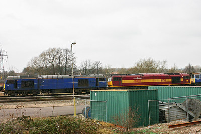 "Two more class 60s with 60011 in Mainline blue livery without any markings and EWS liveried 60003 ""Freight Transport Association"" sit on one of the shed roads at Toton."