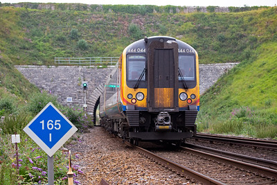 Desiro class 444 unit 444044 passes the site of Upwey Wishing Well halt on the climb of Upwey Bank at 1 in 50 with 1W24 1503 Weymouth to Waterloo.  It is passing through Bincombe No2 tunnel.