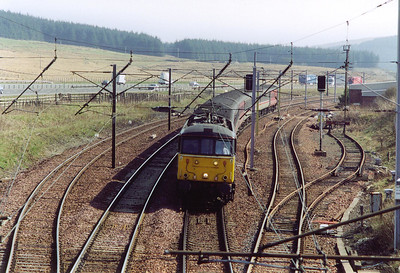 86256 comes over the summit and starts the 1 in 99 descent with its cross country working 1S49 1031 Birmingham International to Edinburgh. On the right is the down passenger loop and cripple siding. On the left is the up passenger loop and the cripple siding.
