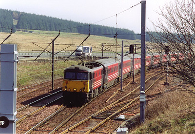 "1S57 is the down ""Royal Scot"" train, 1030 off London Euston to Glasgow Central. 87021 blasts over the top with its rake of mkIII coaches and DVT, shame it wasn't a Duchess!!"