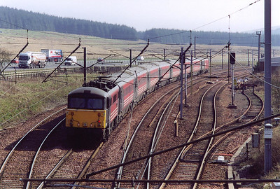 "Beattock is the highest point on the WCML at 1,016 feet above sea level. 87012 breasts the summit propelling its train, the up ""Caledonian"" through the loops and sidings."