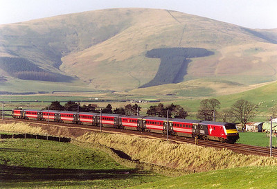 Tewsgill Hill behind Crawford is bathed in warm evening sunshime and forms a wonderful backdrop to an unknown DVT and class 87. The train is climbing at 1 in 142 at this point and the train is 1M34 1700 Glasgow Central to Euston.