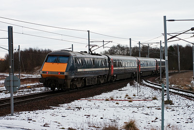 The day was very cold and overcast at this time in the morning with the snow frozen. National Express branded 91102 propels its train over the turnout and adverse camber onto the Edinburgh branch of the former Caledonian Railway's west coast route. The service is 1E07 0750 Glasgow Queen Street to Kings Cross.