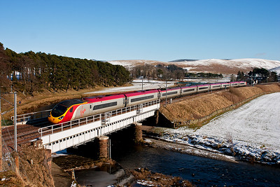 390011 crosses Crawford Bridge. Areas where the sun gets to most has lost the snow, elsewhere it is still quite thick.