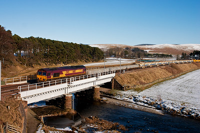 66113 crosses over Crawford Bridge in brilliant winter sunshine with a clear blue sky.