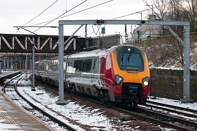 221115 passes through a very cold Carstairs station with 1S34 0557 Crewe to Glasgow Central.