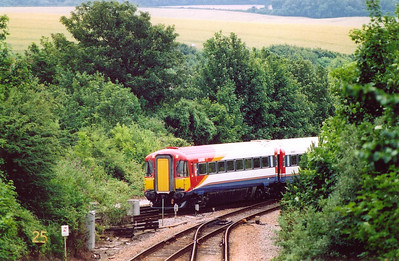 "An unknown class 442 5WES unit passes over the junction at Dorchester where the LSWR joined the GWR who laid the first metals to Weymouth. The train is 1W11 0930 London Waterloo to Weymouth. The signalbox stood in the ""V"" of the tracks.  12/7/2004"