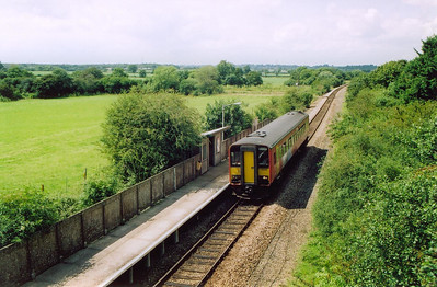 The small halt at Thornford is the setting as bubblecar 153370 runs through with the late running 2O89 1200 off Bristol to Weymouth. This unit may be substituting for another class of unit.  13/7/2004