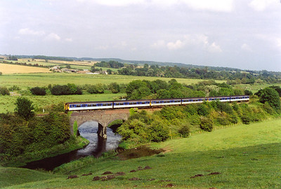 Three class 150 sprinter units pass over the two arch viaduct over a youthful River Frome with 2O90 1433 Bristol to Weymouth.  10/8/2002