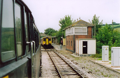 The former Great Western Railway signalbox stands guard over the station but is now boarded up and disused. 31128 leading 2V74 1100 Weymouth to Bristol runs into Maiden Newton while 150236 stands waiting with 2O88 0928 from Bristol to Weymouth.  16/7/2004